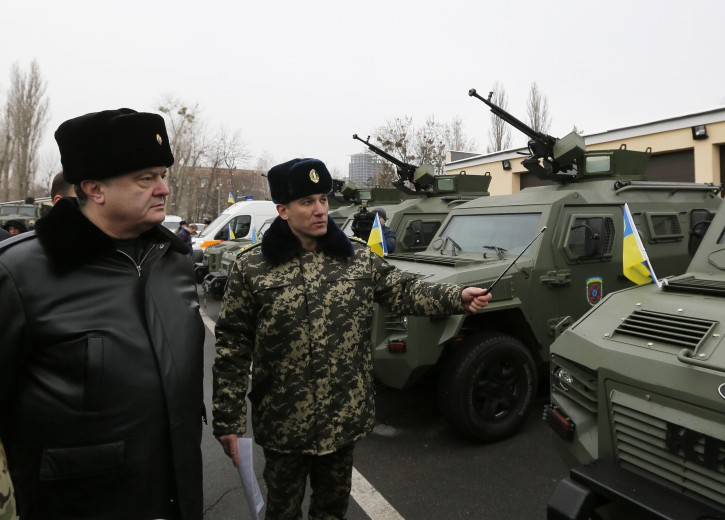Ukrainian President Petro Poroshenko, left, inspects military armored personnel carriers during his visit to the State Border Guard Service in Kiev, Ukraine, Saturday, Feb. 14, 2015. (AP Photo/Sergei Chuzavkov)