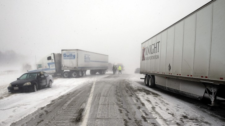 A multi-vehicle accident in near white out conditions, blocks west bound I-70, Saturday, Feb. 14, 2015 west of Columbus, Ohio.  Heavy blowing snow is making travel difficult across Ohio and has caused quite a few accidents on the interstates. (AP Photo/Alex Brandon)