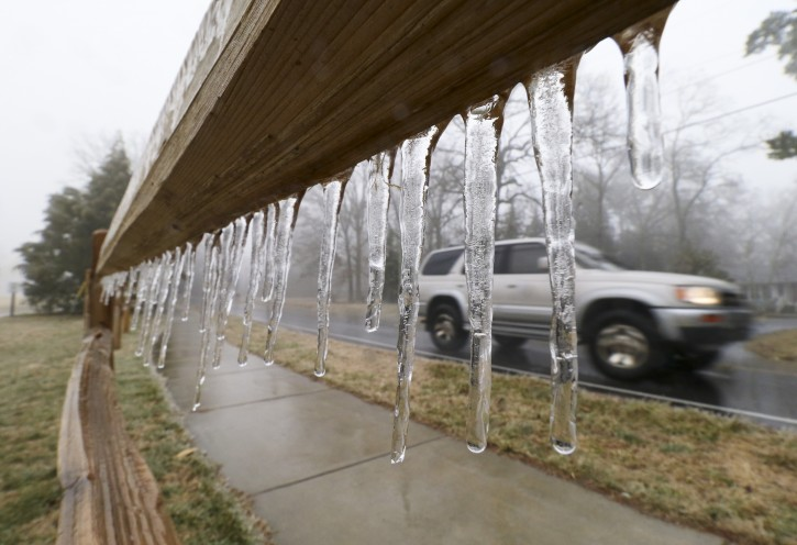 A motorist passes a fence atop Signal Mountain where icicles are forming as rain and freezing temperatures make their way into the Tennessee Valley near Chattanooga, on Monday, Feb.  16, 2015.  (AP Photo/Chattanooga Times Free Press, Dan Henry)