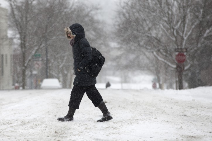 A pedestrian makes their way along Main Street in downtown Ann Arbor, Mich, as more than 2 inches of snow falls on Sunday, Feb. 1, 2015. (AP Photo/The Ann Arbor News, Patrick Record)