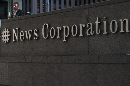A passer-by stands in front of the News Corporation building in New York June 28, 2012. CREDIT: REUTERS/KEITH BEDFORD