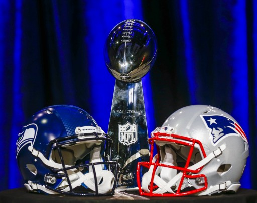 The Vince Lombardi Trophy (C), presented to the winner of the Super Bowl, sits with Seattle Seahawks (L) and New England Patriots helmets in Phoenix, Arizona, USA, 30 January 2015. EPA/TANNEN MAURY
