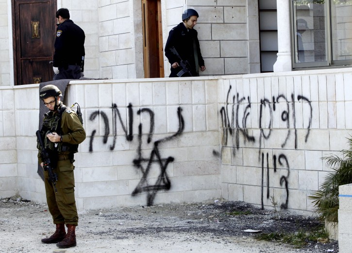 Israeli soldiers and police investigate near a Star of David with the word 'Revenge' written in Hebrew above it on the walls of a mosque in the West Bank village of Jab'a, near Bethlehem, just south of  Jerusalem, that was the scene of an attack and fire apparently carried out by Jewish settlers overnight on 25 February 2015. EPA/ABED AL HASLHAMOUN