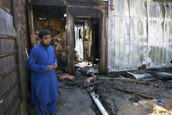 Ahsan Zahid, Assistant Imam, assistant priest in Islam, stands in front of the charred Quba Islam Institute after it burned Friday, Feb. 13, 2015, in Houston. (AP Photo/Houston Chronicle, Cody Duty)