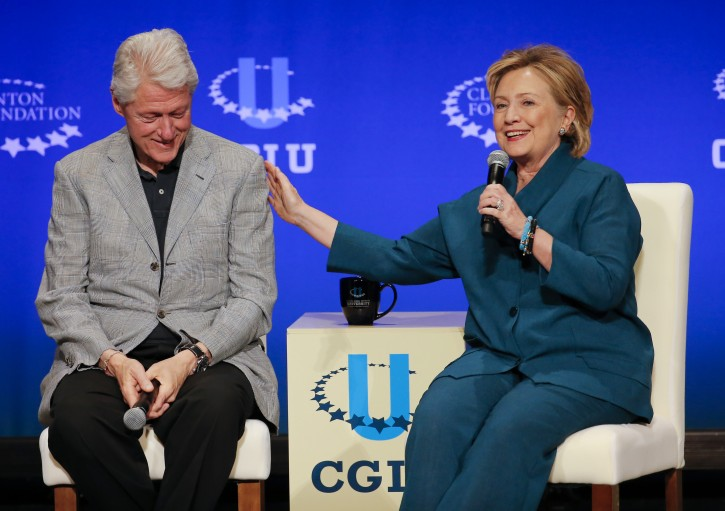 FILE - In this March 22, 2014, file photo, former President Bill Clinton, left, listens as former Secretary of State Hillary Rodham Clinton speaks. (AP Photo/Matt York, File)