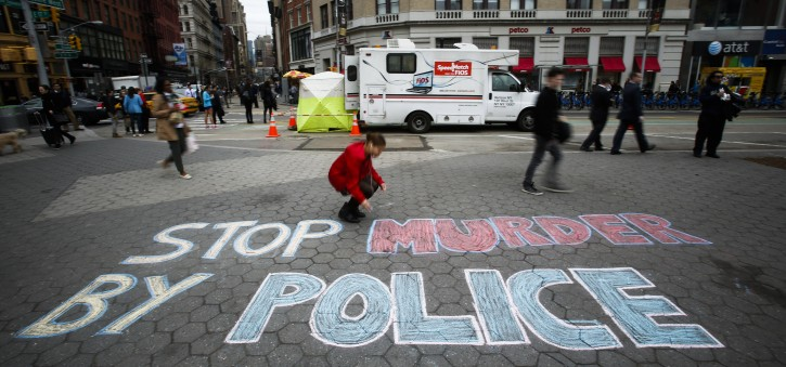 Ashley Hair, 17, writes a message in chalk on the street during a rally against police brutality in New York, New York, USA, 14 April 2015.EPA