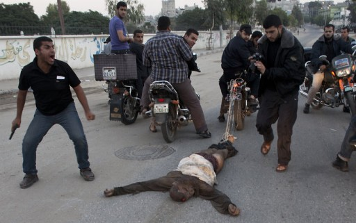 File: Palestinians ride through the streets of Gaza City with the body of a man tied to a motorcycle killed for allegedly working undercover for Israel in Gaza. (Credit: EPA)