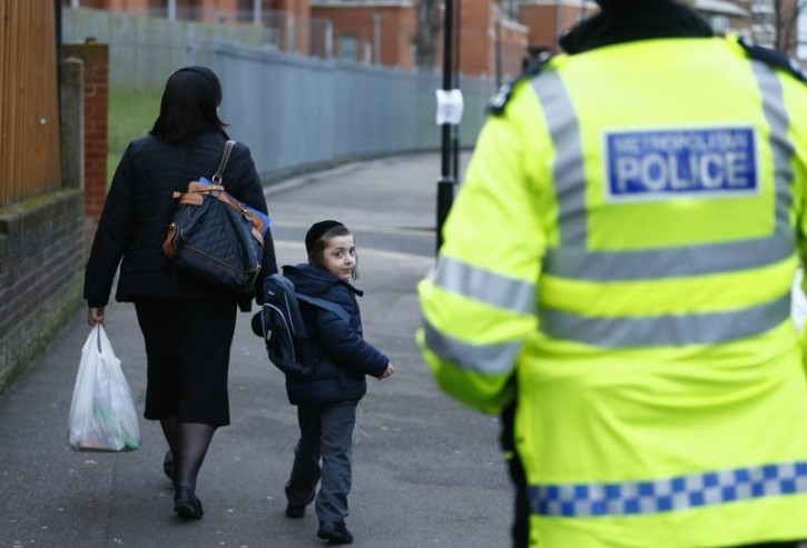 FILE - A young member of the Jewish community looks back at a police officer as he walks in north London January 20, 2015. Reuters