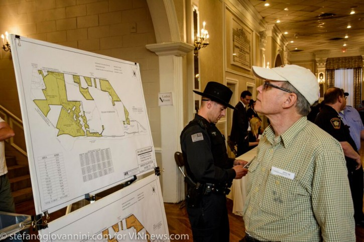 An unidentified man looks up the annexation map at the entrance before the hearing as a law enforcement official  guards the Hall.