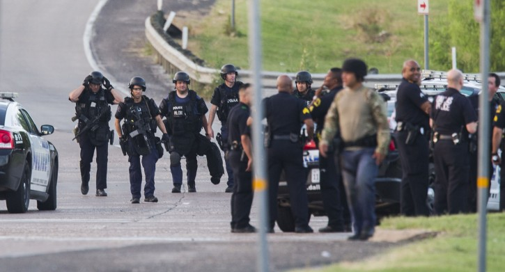 Dallas SWAT  and other police officers gather at the intersection of Interstate 45 and E Palestine Street, where police have cornered a suspect in a van on Saturday, June 13, 2015 in Hutchins, Texas.   Police Chief David Brown says a police sniper has shot the suspect in an overnight attack on police headquarters and that the department is checking to see if he's still alive. Brown says investigators believe the man acted alone in the early-morning attack on Dallas police headquarters, despite early witness reports that others may have taken part.    (Ashley Landis/The Dallas Morning News via AP