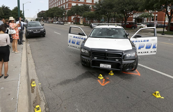 Members of the media look at a police cruiser with bullet holes in the windshield after a gunman opened fire at Dallas Police headquarters Saturday, June 13, 2015, in Dallas. A man suspected of spraying the headquarters with gunfire and planting pipe bombs, early on Saturday, has been found dead in a van after a police sniper shot him, police Chief David Brown said. (AP Photo/Ron Jenkins)