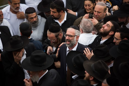 FILE - Gabriel Sassoon reacts near the fresh graves of his seven children during thier funeral in Jerusalem on March 23, 2015. Flash90