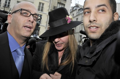 FILE - Fashion designer John Galliano (C) and his lawyer Stephane Zerbib (L) arrive for a hearing at a police station in Paris February 28, 2011.REUTERS