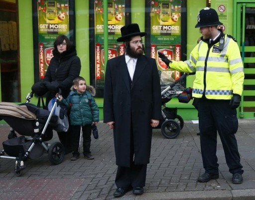 FILE - A police officer waves to a child as members of the Jewish community wait to cross a road in north London January 20, 2015. REUTERS