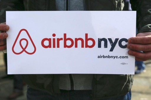 """FILE - A supporter of Airbnb holds a sign during a rally before a hearing called """"Short Term Rentals: Stimulating the Economy or Destabilizing Neighborhoods?"""" at City Hall in New York January 20, 2015. REUTERS/Shannon Stapleton"""