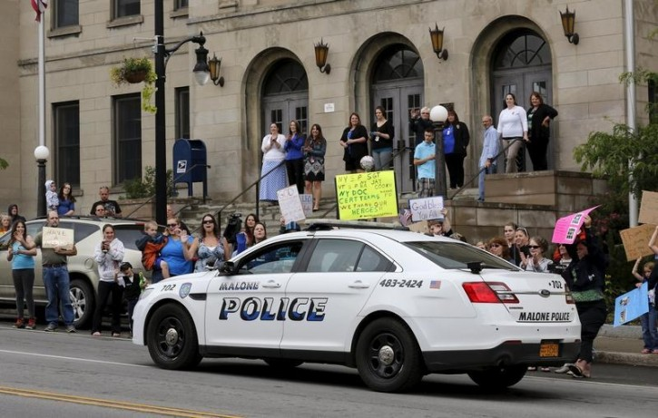 People cheer as a Malone police vehicle passes by during a rally in support of law enforcement following the capture of David Sweat, in Malone, New York June 29, 2015. Reuters