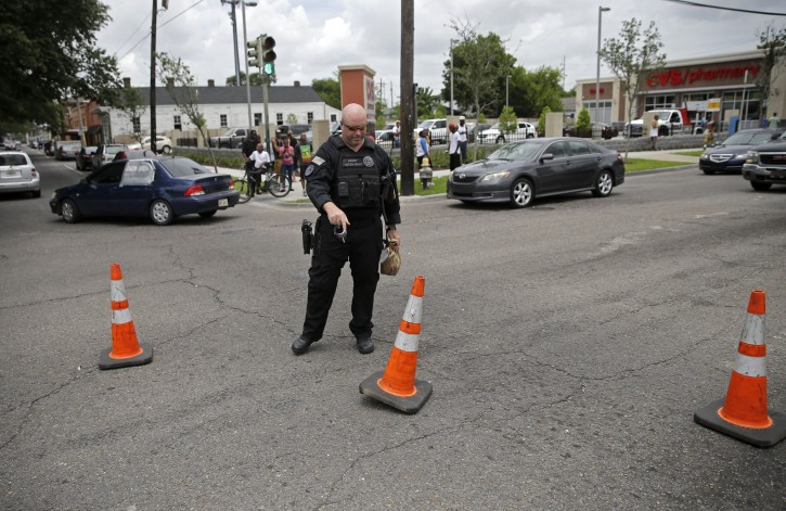 A police officer places cones to divert traffic at the scene where a New Orleans Police officer was shot and killed while transporting a prisoner in New Orleans, Saturday, June 20, 2015. The prisoner remains at large. (AP Photo/Gerald Herbert)