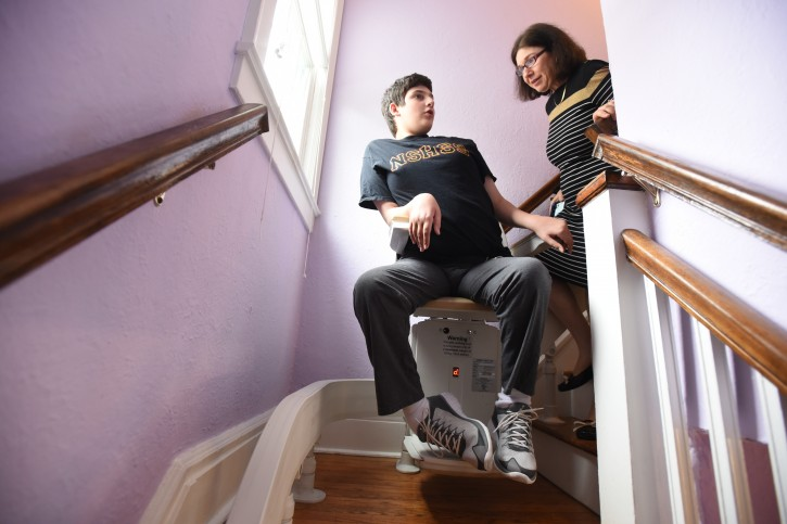 Esther and her son Tavi 18 as she helps him go downstairs on his chair lft.   --  CHRIS PEDOTA / THE RECORD