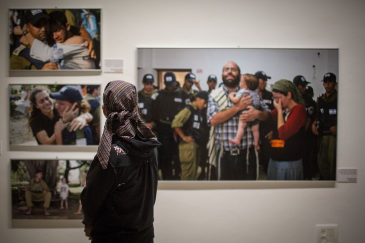 Israelis view the exhibition of press photographs of the forced evacuation of the Gush Katif settlements in Gaza in 2005, taken by photographers of the Israeli daily newspaper, Yediot Aharnot, at the First Station in Jerusalem, on July 21, 2015. This week, Israel marks the 10 year anniversary of the disengagement from Gaza. Photo by Hadas Parush/Flash90