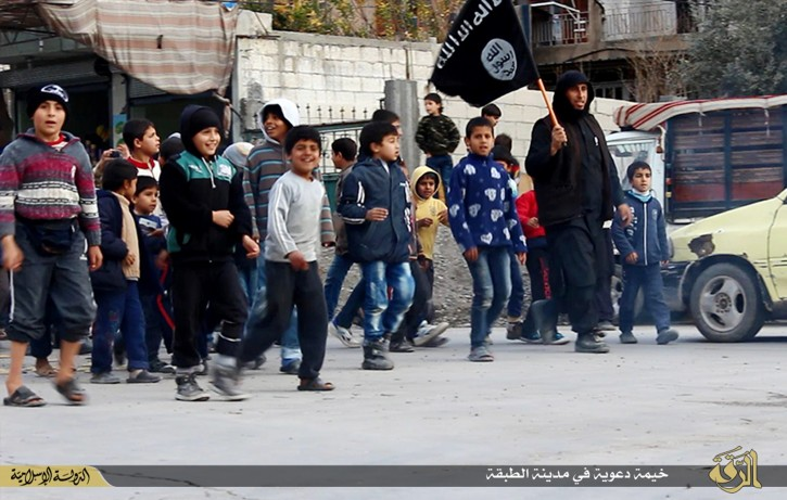 In this photo released on Jan. 14, 2015, by a militant website, which has been verified and is consistent with other AP reporting, Syrian boys, left, follow an Islamic State militant, right, holding his group's flag, during a street preaching session in al-Tabqa in Raqqa province, northeast Syria. IS extremists have made it a priority to mold children under their rule into a new generation of militants, luring them into becoming fighters, suicide bombers and executioners. (Militant website via AP)