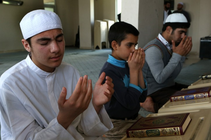 In this April 19, 2015 picture, young Syrians pray as they attend a religious class at an Islamic teaching center designed to counter Islamic State group indoctrination, near the Turkish-Syrian border city of Sanliurfa, southern Turkey. (AP Photo/Hussein Malla)
