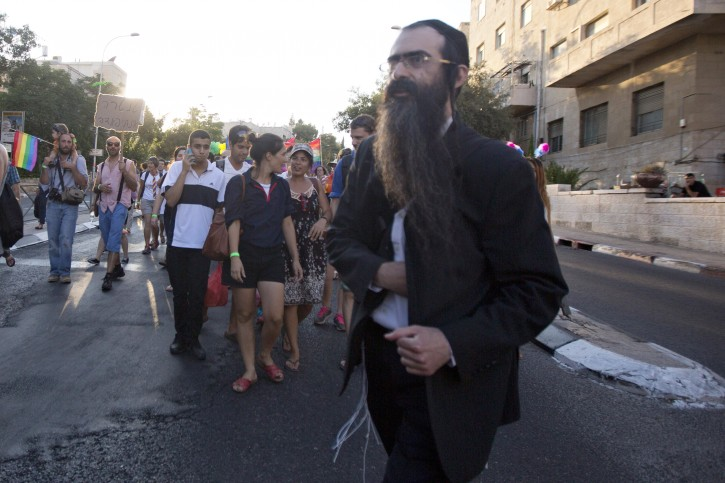 Ultra-Orthodox Jew Yishai Schlissel walks through a Gay Pride parade and is just about to pull a knife from under his coat and start stabbing people in Jerusalem, Thursday, July 30, 2015. (AP Photo/Sebastian Scheiner)