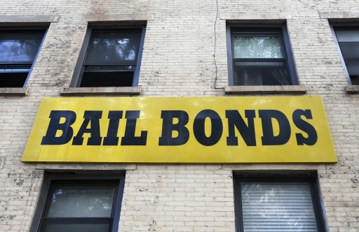 In this photo taken Tuesday, July 7, 2015, a bail bonds sign hangs on the side of a bail bonds business near Brooklyn's courthouse complex and jail in New York. (AP Photo/Kathy Willens)