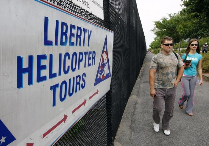 FILE - Two people walk past a sign pointing to the Liberty Helicopter Tours company in New York, August 8, 2009.  Reuters