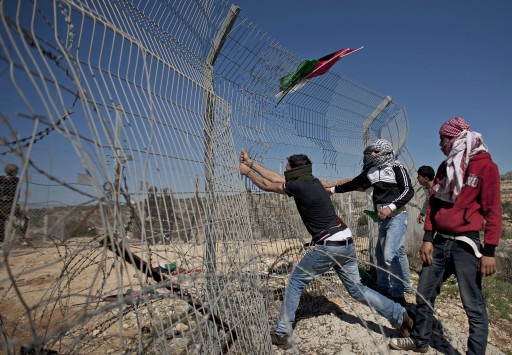 File: Palestinian men try to tear down the fence marking the border between Israel and Palestine. EPA/OLIVER WEIKEN