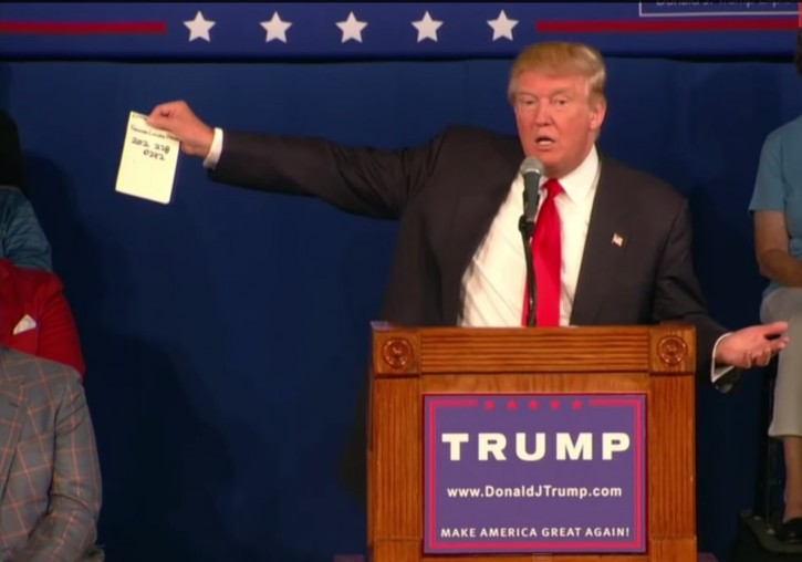 FILE - Republican presidential hopeful Donald Trump holds up a sheet of paper as he talks about calling Republican presidential candidate, Sen. Lindsey Graham, R-S.C., during his South Carolina campaign kickoff rally in Bluffton, S.C., Tuesday, July 21, 2015.