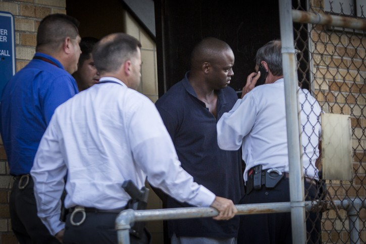 Shannon J. Miles, 30, is walked out of the Harris County Sheriff's Department in Houston on Saturday, Aug. 29, 2015. Prosecutors on Saturday charged Miles with capital murder in the killing of a uniformed sheriff's deputy who was gunned down from behind while filling his patrol car with gas. (Marie D. De Jesus/Houston Chronicle via AP)