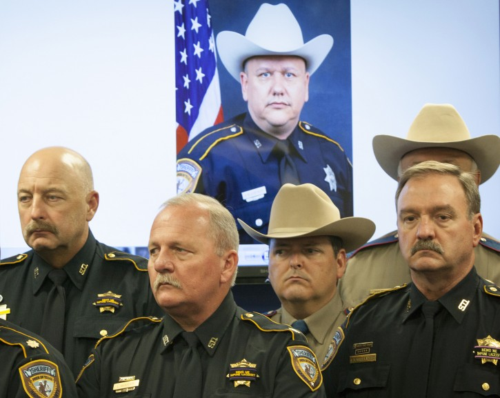 Law enforcement officers attend a news conference regarding the shooting death of Harris County Sheriff's Deputy Darren Goforth, pictured in back, Saturday, Aug. 29, 2015, in Houston. Prosecutors on Saturday charged Shannon J. Miles with capital murder in the Friday killing of Goforth at a suburban Houston gas station. (Marie D. De Jesus/Houston Chronicle via AP)