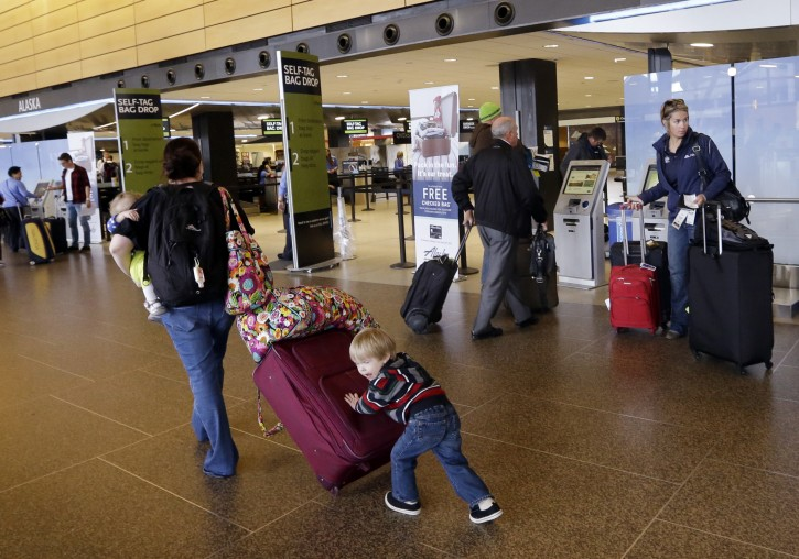 In this March 24, 2015, photo, Colin Drummond, 4, pushes luggage from behind as he walks with family members to check-in a relative for an Alaska Airlines flight at Seattle-Tacoma International Airport in SeaTac, Wash. Fliers in certain markets are seeing bargain flights as fare wars make a limited return. (AP Photo/Elaine Thompson)