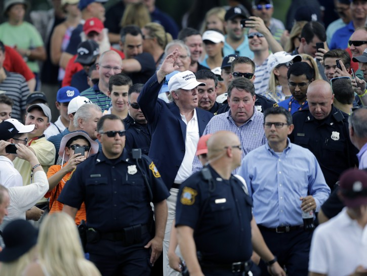 Republican presidential candidate Donald Trump, center, waves as he walks with a crowd during the final round of play at The Barclays golf tournament Sunday, Aug. 30, 2015, in Edison, N.J. (AP Photo/Mel Evans)