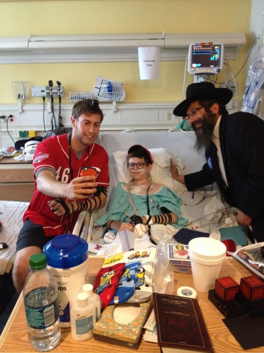 Jon Moscot, a rookie pitcher for the Cincinnati Reds, wrapped tefillin with Avi Newhouse, who is undergoing treatment for a rare form of lymphoma in a Cincinnati hospital.(Chabad.org)