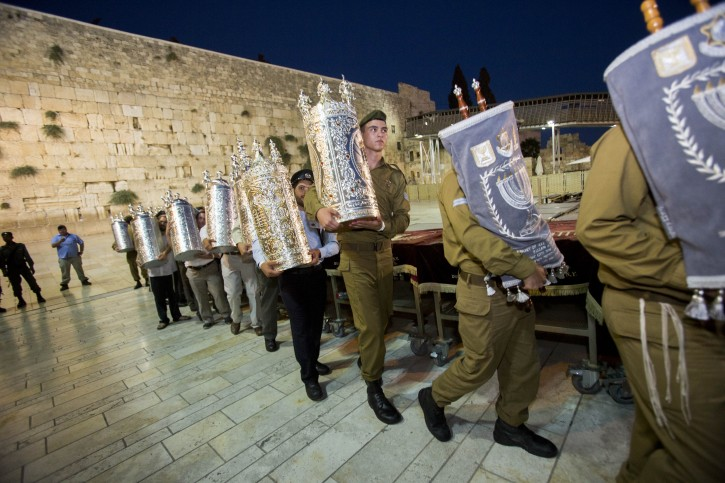 Israeli security forces members hold Torah scrolls during a ceremony with 75 Torah scrolls from around the world in memory of the soldiers killed in Operation Protective Edge and in Israel's wars at the Western Wall in Jerusalem Old City on August 12, 2015. Photo by Yonatan Sindel/Flash90
