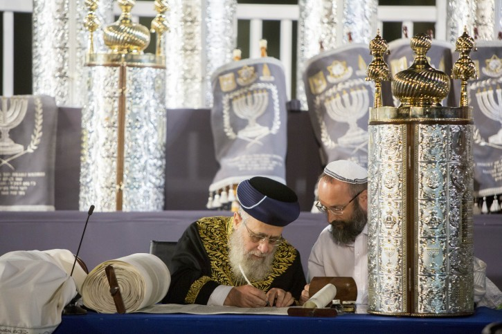 Chief Sephardi rabbi Yitzhak Yosef writes the last letter in a torah scroll during a ceremony with 75 Torah scrolls from around the world in memory of the soldiers killed in Operation Protective Edge and in Israel's wars at the Western Wall in Jerusalem Old City on August 12, 2015. Photo by Yonatan Sindel/Flash90