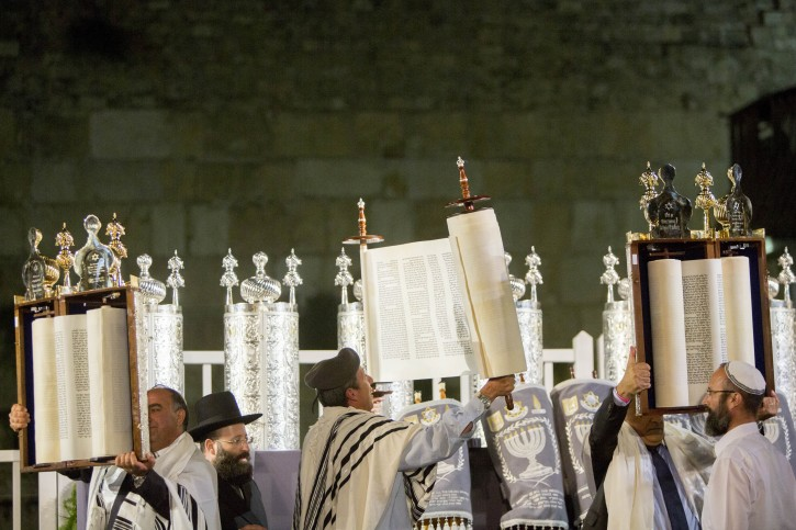 Israelis lift Torah scrolls during a ceremony with 75 Torah scrolls from around the world in memory of the soldiers killed in Operation Protective Edge and in Israel's wars at the Western Wall in Jerusalem Old City on August 12, 2015. Photo by Yonatan Sindel/Flash90