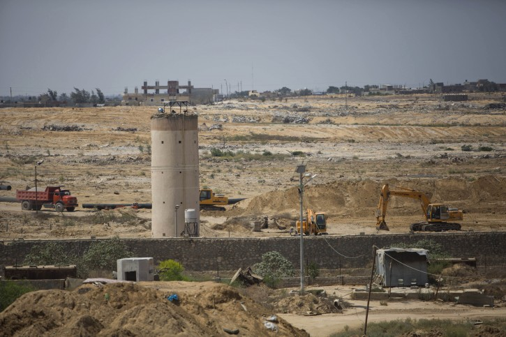 In this Sunday, Aug. 30, 2015 photo, bulldozers and diggers work on the Egyptian side of the border with the Gaza Strip. (AP Photo/Khalil Hamra)