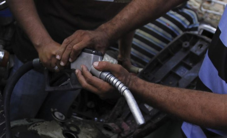 People jostle for a pump nozzle at a petrol station during a fuel shortage in Cairo June 26, 2013.  AP