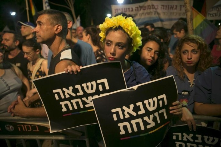 "A woman holds signs during a protest against the violence towards the gay community in Tel Aviv August 1, 2015. Thousands came to show solidarity after an ultra-Orthodox Jewish man stabbed and wounded six participants, two of them seriously, in the annual Gay Pride parade in Jerusalem on Thursday, with police saying the suspect was jailed for a similar attack 10 years ago. The sign reads ""hatred kills"".  REUTERS/Baz Ratner"