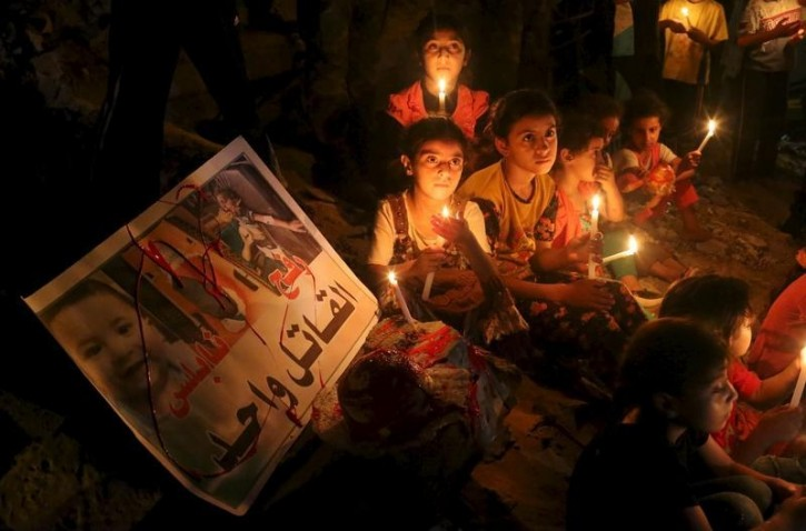 Palestinian children light candles during a rally to remember 18-month-old Palestinian baby Ali Dawabsheh, who was killed after his family's house was set on fire in a suspected attack by Jewish extremists, in Rafah in the southern Gaza Strip August 2, 2015. REUTERS