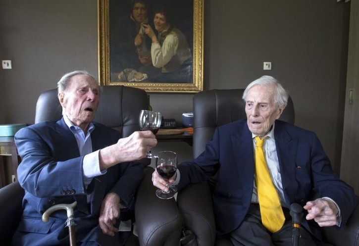 The world's oldest living twin brothers, Paulus (L) and Pieter Langerock from Belgium, 102, toast while sitting in their living room at the Ter Venne care home in Sint-Martens-Latem, Belgium, August 11, 2015. REUTERS