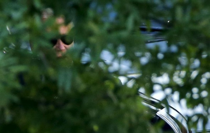 U.S. Vice President Joe Biden (C) can be seen through trees as he arrives to attend the presidential daily briefing at the White House in Washington August 24, 2015.