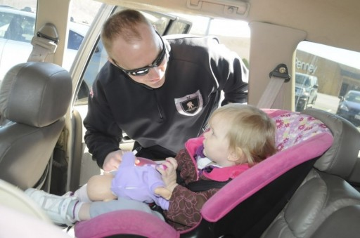FILE - A Maryland State Police trooper ensures that a child's car seat is installed correctly at a safety seat check in Cumberland, Md. (Steven Bittner/Cumberland Times-News via AP)