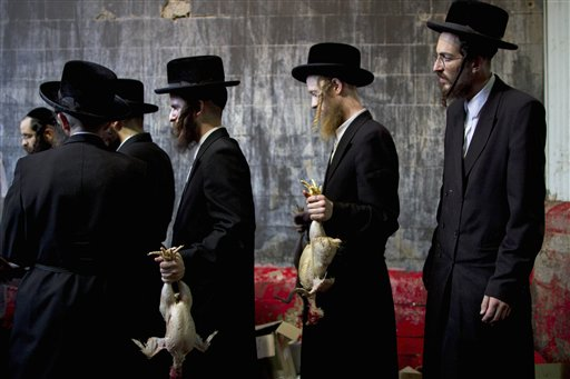FILE - In this picture taken Wednesday, Oct. 5, 2011, ultra-Orthodox Jewish men hold chicken after it was slaughtered in Bnei Brak, Israel. (AP Photo/Oded Balilty)