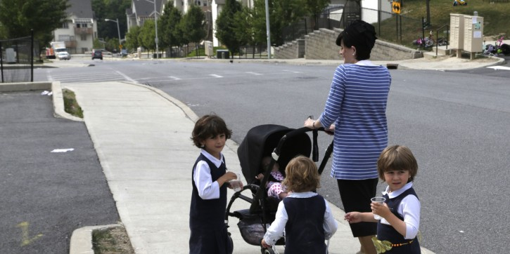 A Hasidic woman walks with her children on Tuesday, July 1, 2014, in Kiryas Joel, N.Y. Kiryas Joel is a tightly packed Hasidic enclave surrounded by suburbia in the Hudson Valley. A petition to expand the village by annexing 500 acres of leafy lots nearby has heightened tensions with some suburban neighbors. There are fears it would lead to unwanted increases in people, homes and traffic. (AP Photo/Mike Groll)