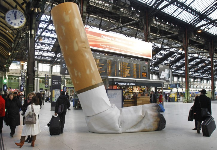 FILE - This Tuesday Dec. 4, 2012 file photo shows a symbolic cigarette butt setting up inside Gare de Lyon railway station in Paris, France as part of a publicity campaign against rudeness by Paris's public transport authority. The city of Paris, littered with 350 tons of cigarette butts each year, is striking back at smokers with a new 68-euro ($76) fine. Starting Thursday, anyone caught flicking their butt onto the sidewalk should be ticketed. (AP Photo/Remy de la Mauviniere, File)
