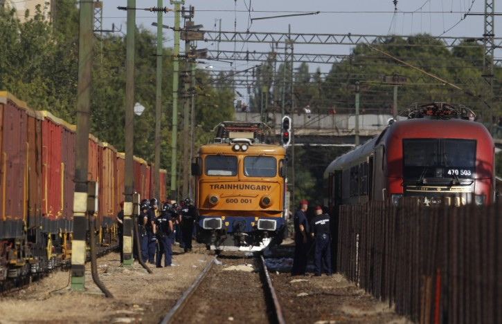 Police try to secure a train that was stopped in Bicske, Hungary, Friday, Sept. 4, 2015. Over 150,000 migrants have reached Hungary this year, most coming through the southern border with Serbia. Many apply for asylum but quickly try to leave for richer EU countries. (AP Photo/Petr David Josek)