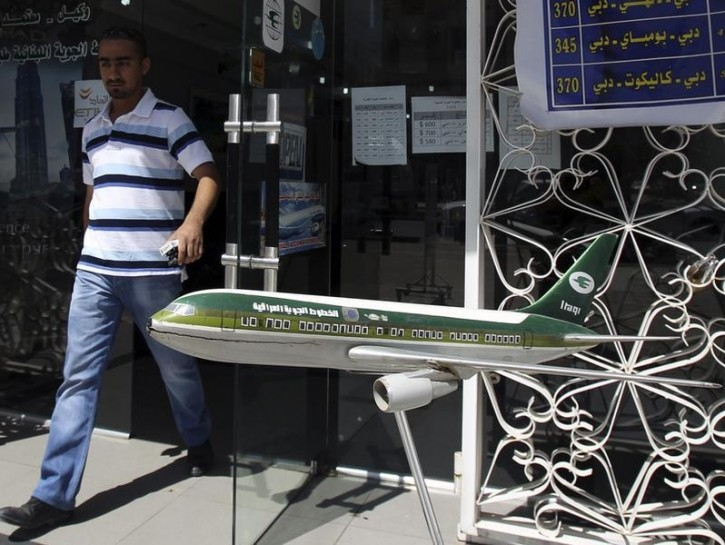 FILE - A customer walks past an Iraqi Airways model plane displayed outside the airline's office in Baghdad May 26, 2010. Reuters